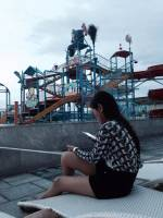 girl, sitting, busy, texting, at sky water park