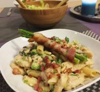 Penne alla carbonara with chicken, pancetta, mushrooms, broccoli, green peas topped with parmesan cheese, bacon bits and asparagus wrapped with bacon.